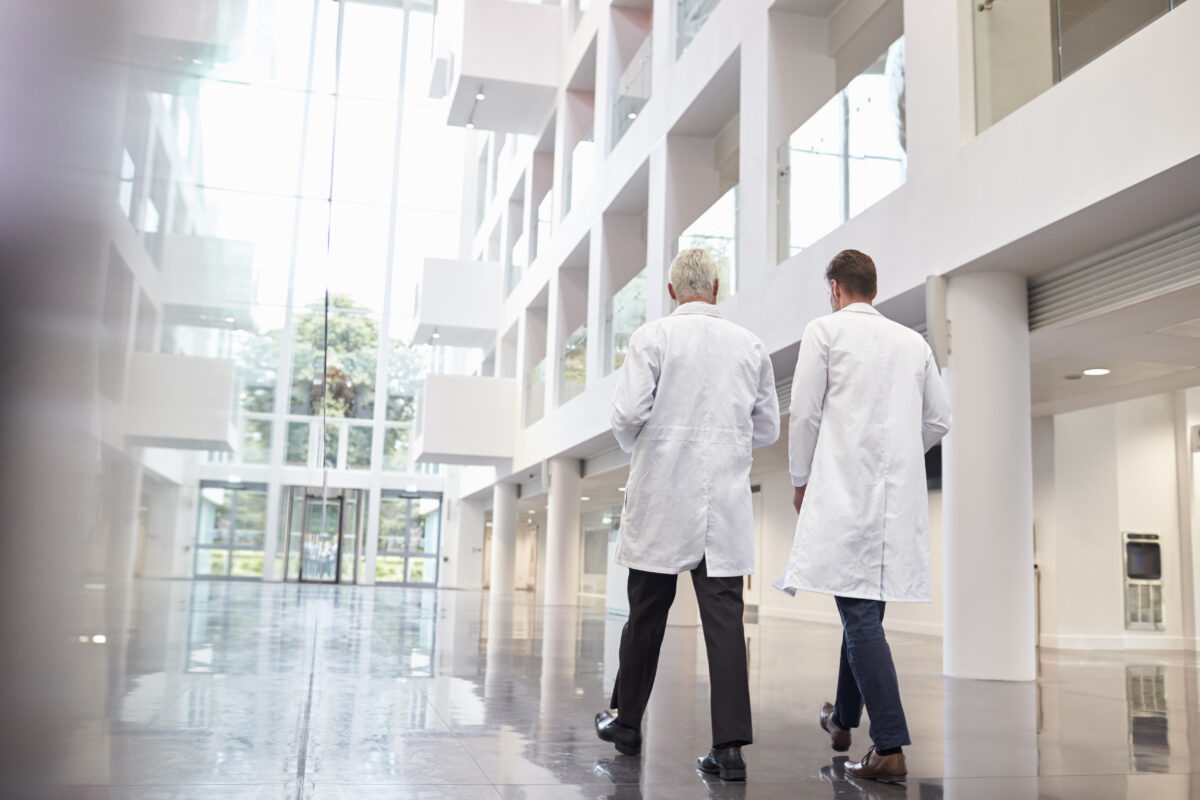 Picture of two doctors walking in a hospital hallway to the door